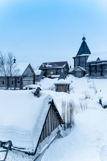 Snow covered houses and buildings against clear sky