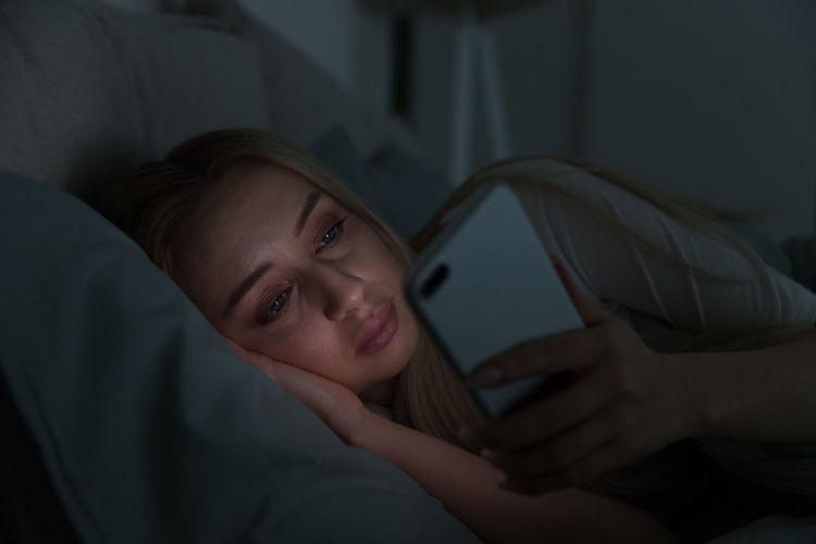 Close-up of woman using smart phone while lying on bed at home
