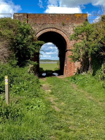 Railway viaduct near Colchester. Arch Architecture Beauty In Nature Built Structure Cloud - Sky Day Grass Green Color Growth Nature Nature Trail No People Outdoors Plant Railway Track Railway Viaduct Signpost Sky Tree