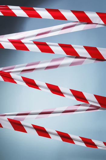 Red and white plastic barrier tape blocking the way. Caution Criss Cross Forbidden Secured Trespassing Ahead Barricade Barrier Barrier Tape Blocking  Bundary No People Prohibited Striped
