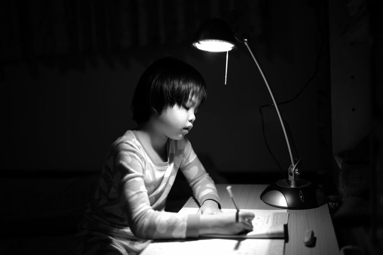 Girl Studying In Darkroom At Home