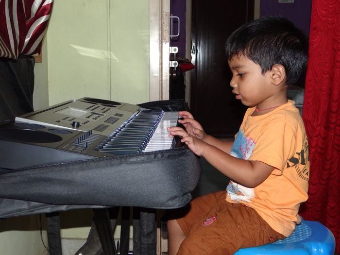 Side view of boy playing piano