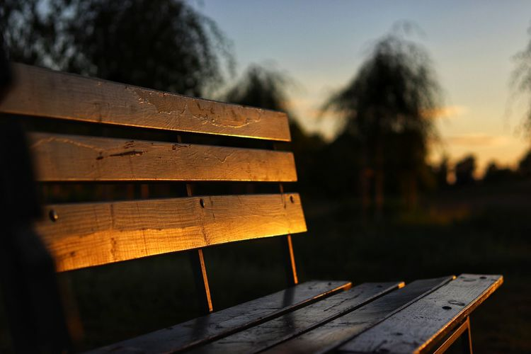 Close-Up Of Empty Bench During Sunset