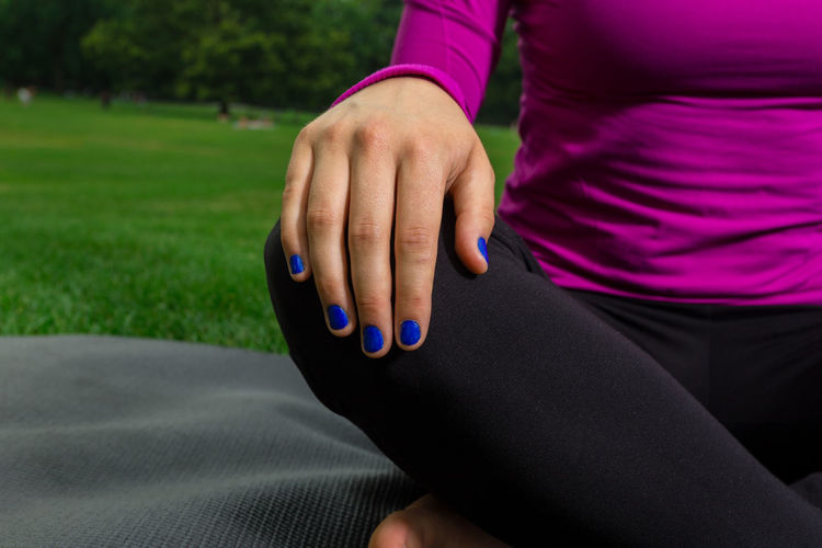Midsection Of Woman Practicing Yoga At Park