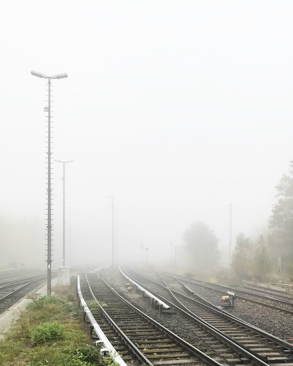 HIGH ANGLE VIEW OF RAILROAD TRACKS AGAINST SKY DURING FOGGY WEATHER