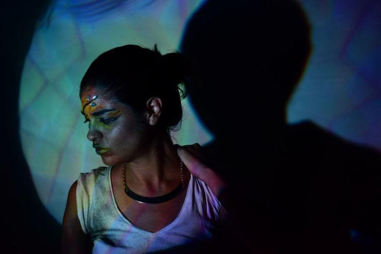 Light falling on woman looking down in darkroom