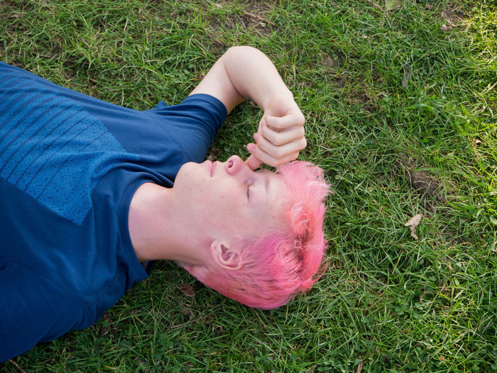 High angle view of teenage boy lying on grassy land