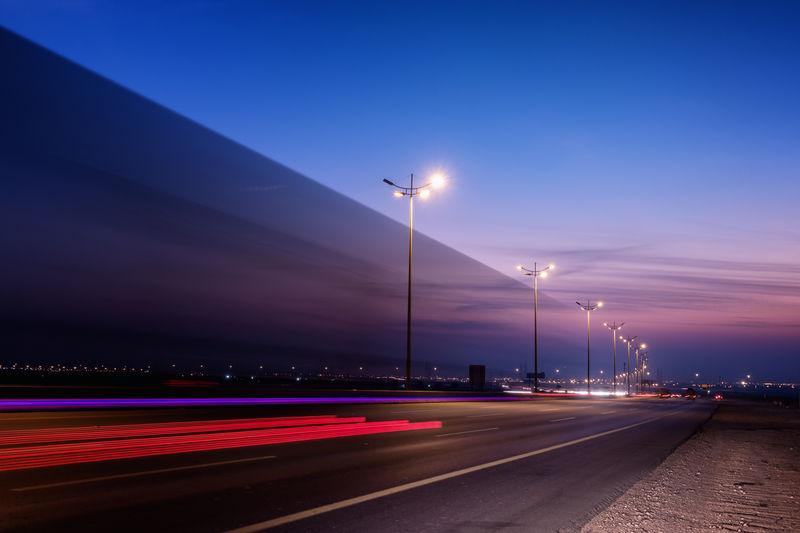 Light Trails On Illuminated Street Against Sky At Dusk