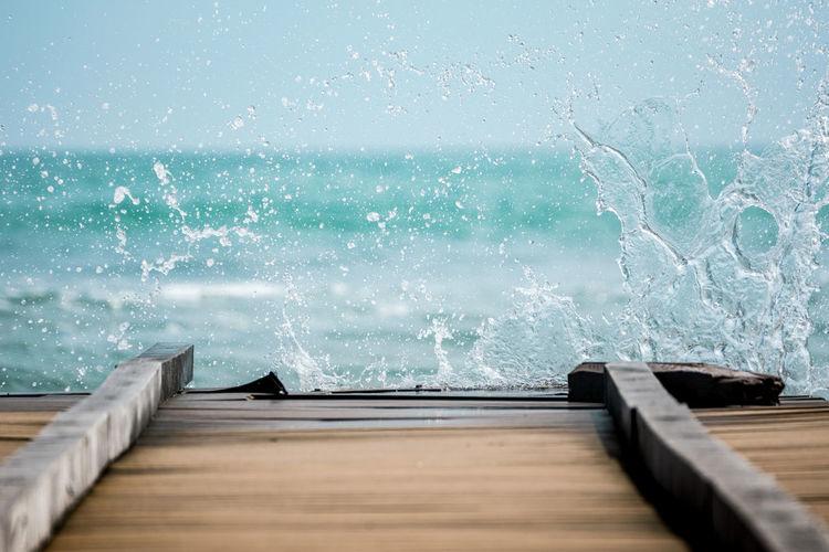 Water splashing on swimming pool against sea