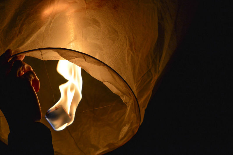 Cropped hand holding illuminated paper lantern at night