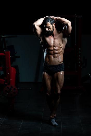 Full length of shirtless man standing on floor