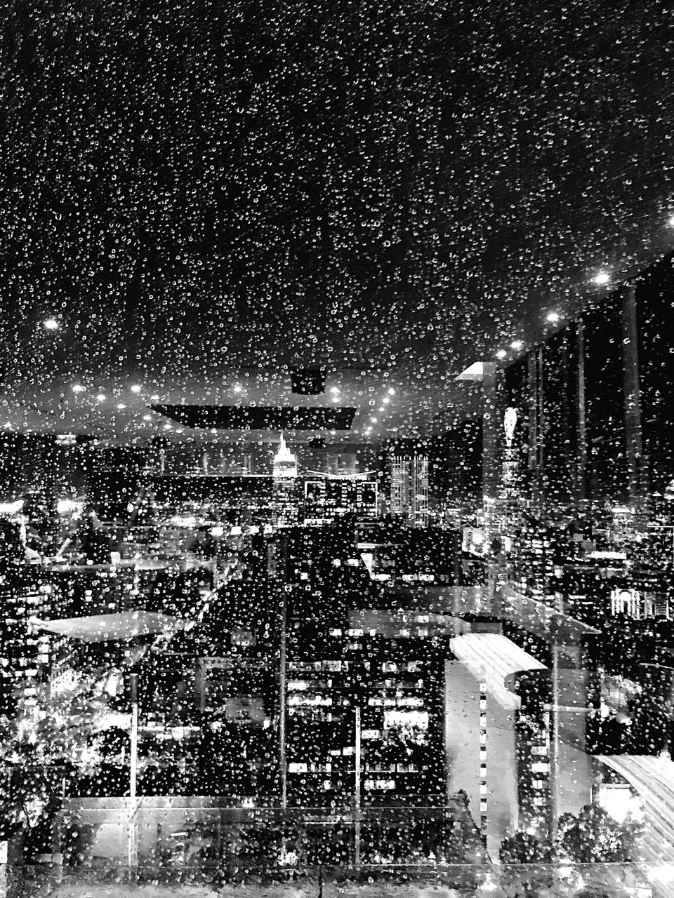 night, snow, built structure, building exterior, architecture, illuminated, snowing, cold temperature, winter, city, nature, no people, building, blizzard, sky, outdoors, extreme weather, street, lighting equipment, cityscape, skyscraper, office building exterior