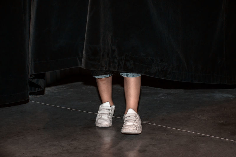 Low Section Of Woman Standing On Floor Behind Curtain