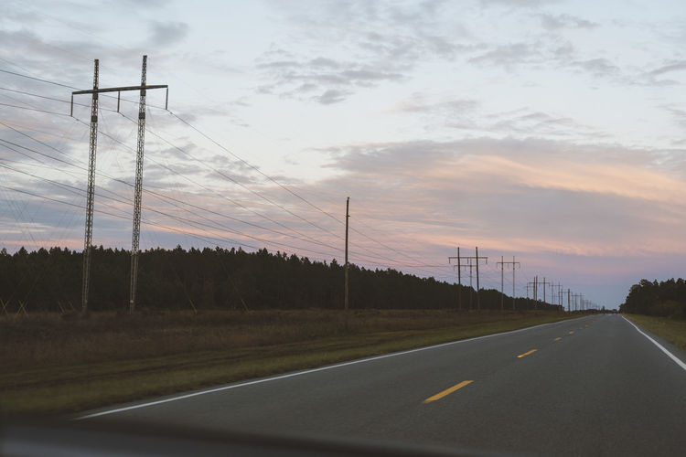 Road by electricity pylon against sky during sunset