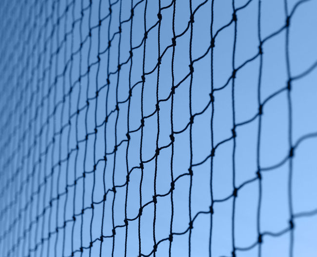 Close-up of fence against blue sky