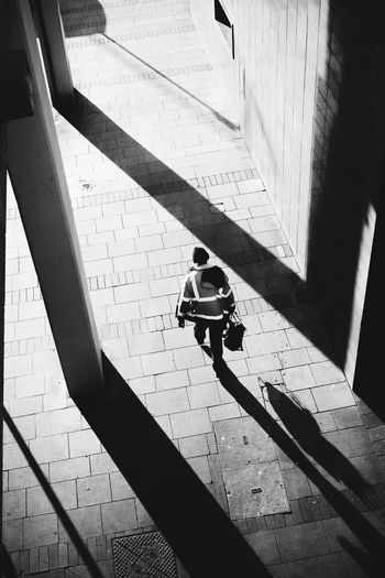 High angle view of worker walking on footpath