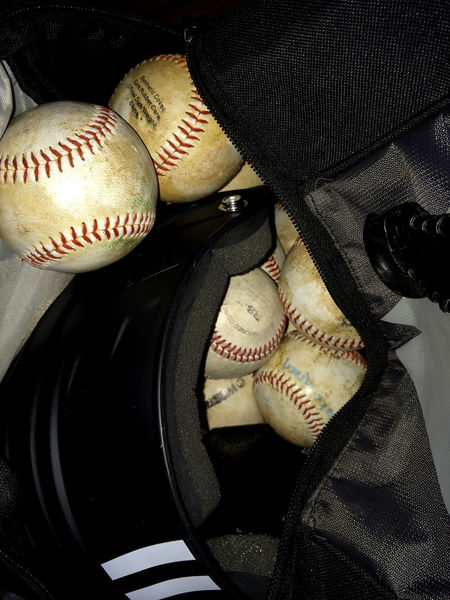 baseballs and helmet used and ready for the first practice to begin. Arrangement Backpack Ball Baseball Black Brown Close Up Detail Directly Above Dirty Focus On Foreground Gray Helmet Jumbled Large Group Of Objects Red Stitches White