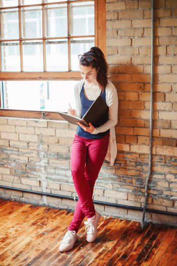 Woman drawing in book while standing by wall