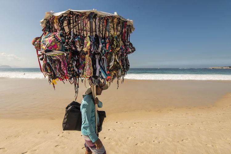 Vendor on beach against sky