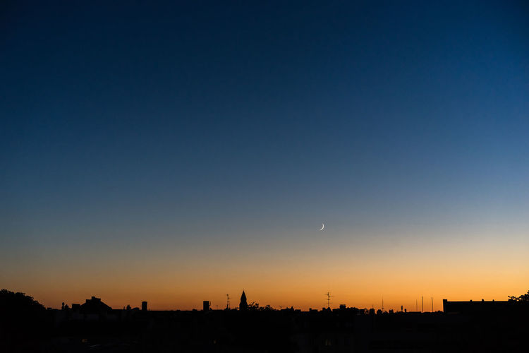 Silhouette cityscape against clear sky during sunset