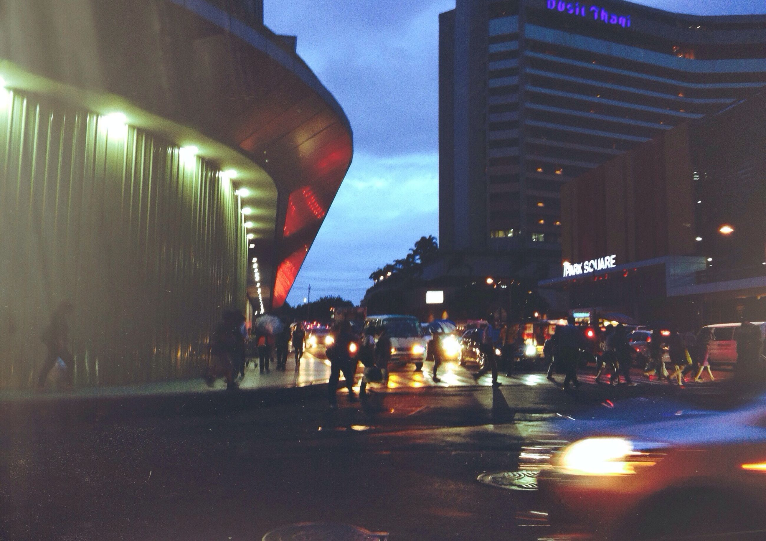 illuminated, night, architecture, building exterior, built structure, city, street, transportation, street light, city life, car, city street, road, land vehicle, sky, lighting equipment, mode of transport, incidental people, travel, dusk