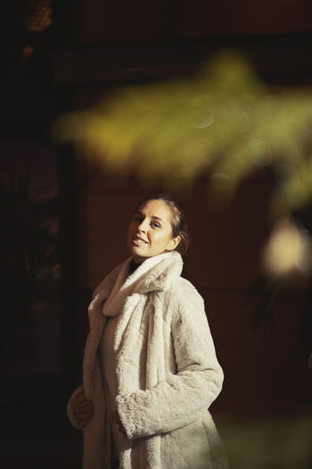 Portrait of young woman wearing warm clothing while standing outdoors