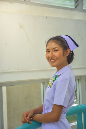 Smiling Young Nurse Standing Against Wall