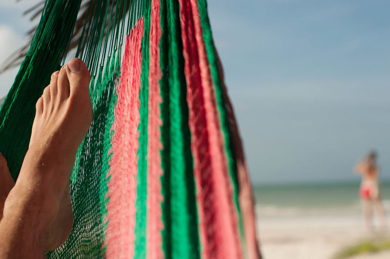 Low section of person relaxing on hammock at beach against sky