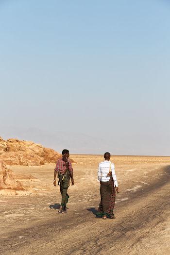 Rear view of men walking on desert