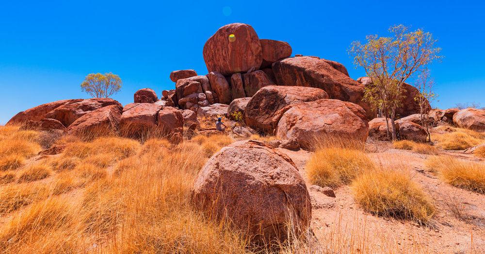 Rock formation on landscape against blue sky