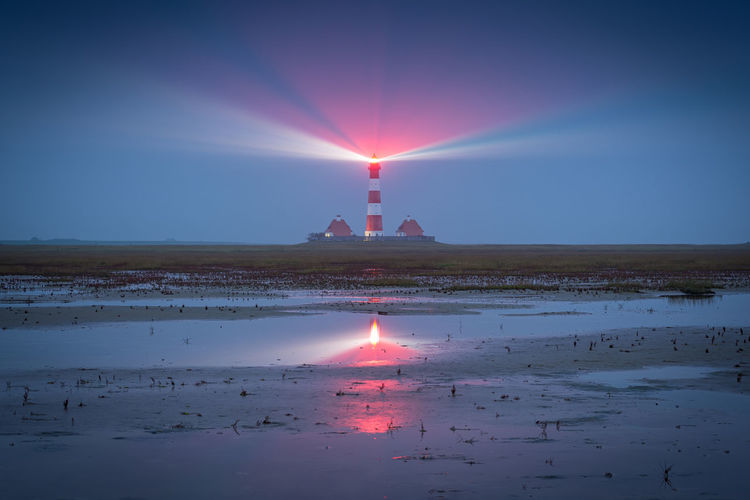 View of lighthouse at seaside during sunset