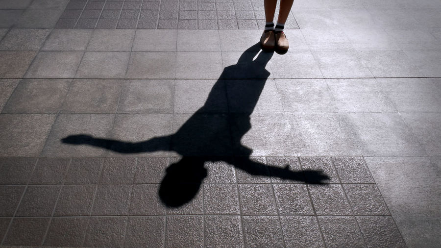 Low section of man walking on footpath with shadow