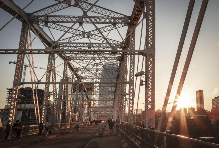 People walking on bridge against sky in city during sunset
