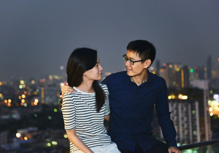Couple sitting on railing against illuminated city at dusk