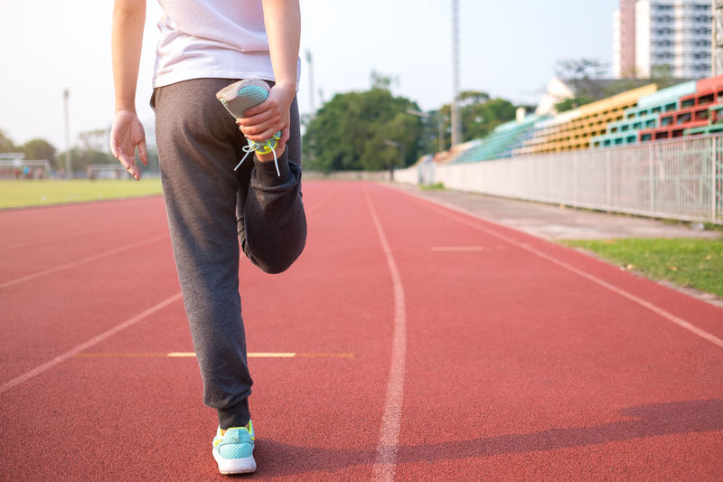 Low Section Of Woman Stretching On Running Track