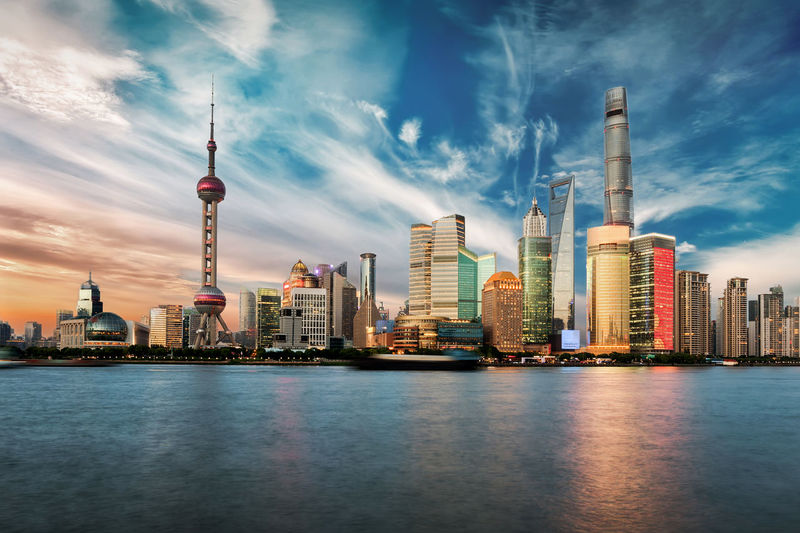 Low angle view of oriental pearl tower amidst buildings by sea against sky