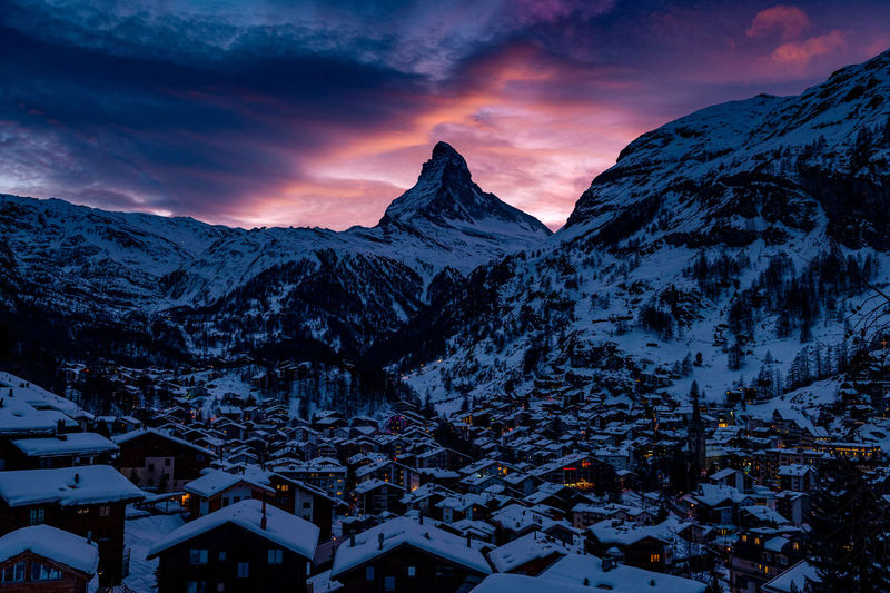 Snow covered houses and mountains against sky during sunset