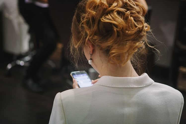 Rear View Real People Headshot One Person Women Human Hair Lifestyles Close-up Indoors  Young Adult Young Women Day Mobile Device Screen Smartphone Business Texting Hairstyle Party Communication