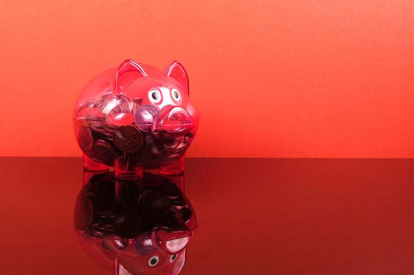 Saving concept with red piggy bank on red background. Piggy Bank Animal Representation Art And Craft Celebration Close-up Coin Colored Background Conceptual Photography  Creativity Decoration Disguise Holiday Indoors  Investment Mask No People Red Red Background Representation Saving Concept Still Life Studio Shot Table Toy Wall - Building Feature