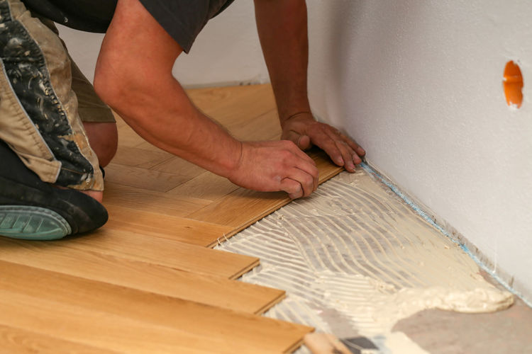 Midsection of carpenter making parquet floor