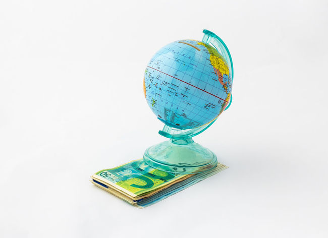 A money box made in the form of a globe, the planet Earth with a money slot at the top stands on a stack of Israeli banknotes of different value isolated on a white background. Business Currency Earning Earth Isolated Art Bank Banknote Buy Cash Coin Coins Design Exchange Finance Globe Israel Money Pay Planet Shekel Stock Studio Shot Wealth White Background