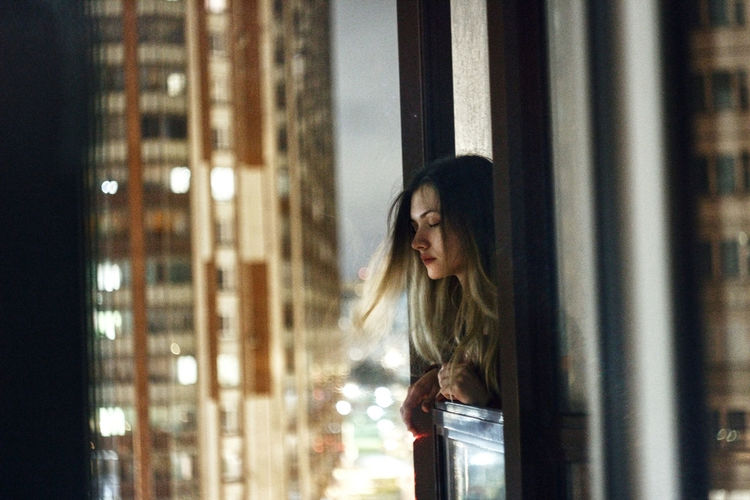 Young woman standing by window at night