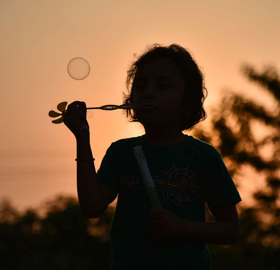 Silhouette girl blowing bubbles against sky during sunset