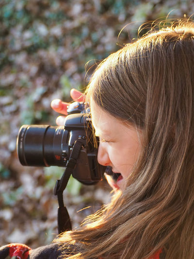 Close-up of girl photographing with camera