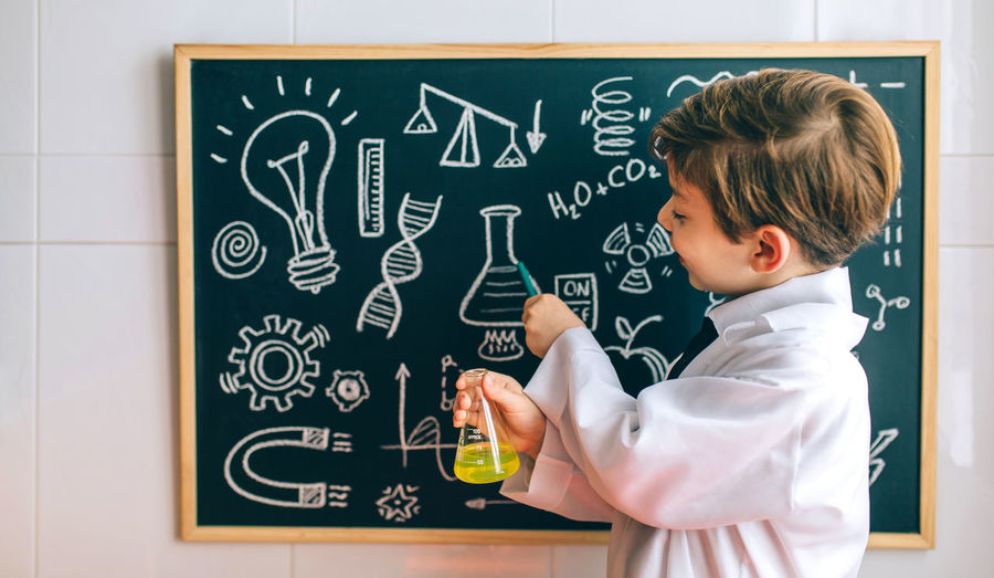 Cute Boy Examining Chemical In Classroom