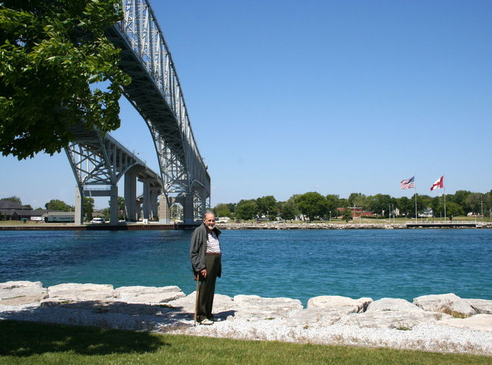 Man standing on pavement against bridge at port huron
