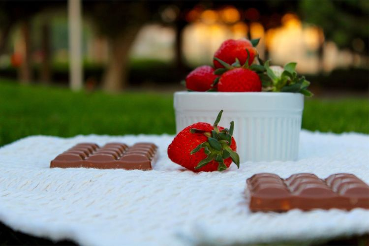 Strawberries with chocolate bars on fabric at lawn