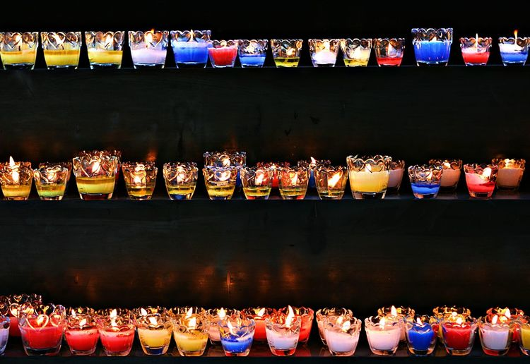 View of illuminated candles on shelf