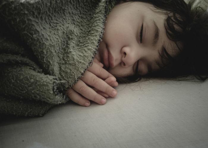 Portrait of cute baby sleeping on bed