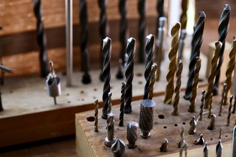High angle view of drill bits in wood on table